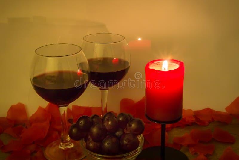 Rotweingläser, Trauben, brennende Kerze und Rosenblätter auf Tabelle lizenzfreie stockfotografie