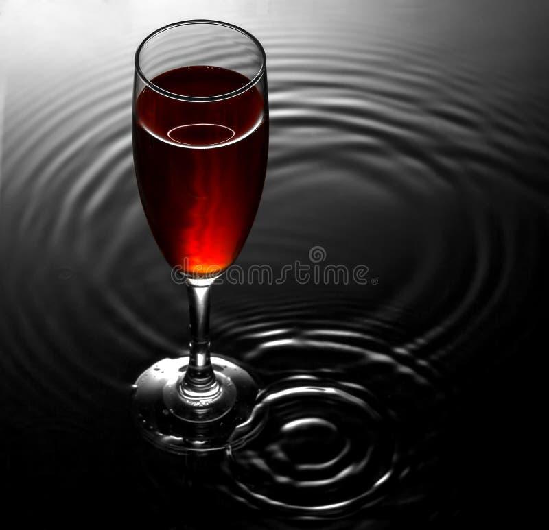 Rotweinglas auf Wasser plätschert Hintergrund lizenzfreie stockfotografie