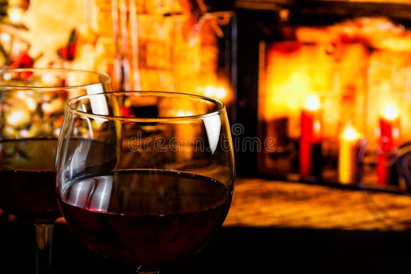 Rotweinglas gegen Weihnachtslicht-Dekorationshintergrund stockfotos