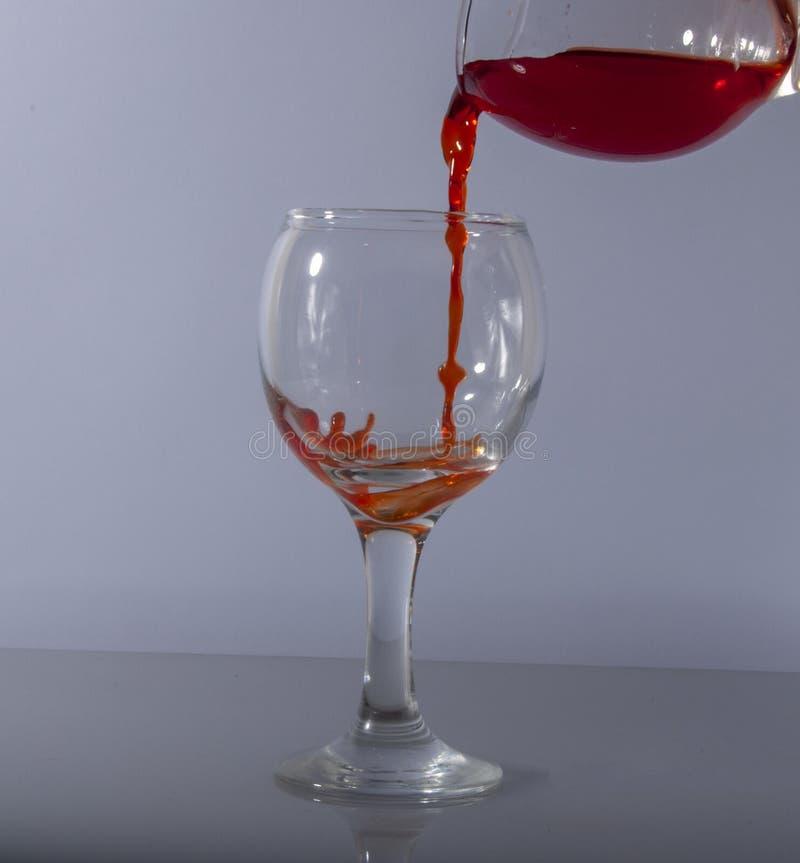 Rotweinspritzen im Glas auf weißem Hintergrund lizenzfreie stockbilder