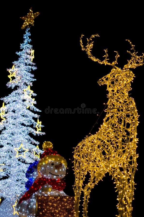 Rotwild mit Schneemann-und Weihnachtsbaum-Dekorations-Lichtern stockfotos