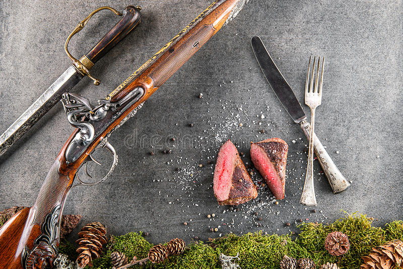 Rotwild- oder Wildbretsteak mit antikem Gewehr, Tischbesteck und Bestandteile mögen Seesalz und -pfeffer, Lebensmittelhintergrund lizenzfreie stockbilder