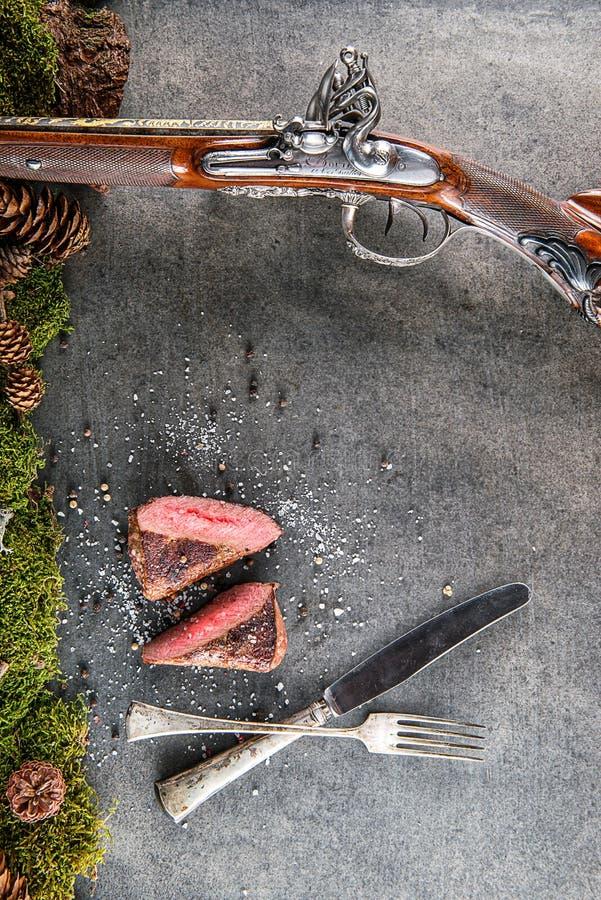 Rotwild- oder Wildbretsteak mit antikem Gewehr, Tischbesteck und Bestandteile mögen Seesalz und -pfeffer, Lebensmittelhintergrund stockfoto