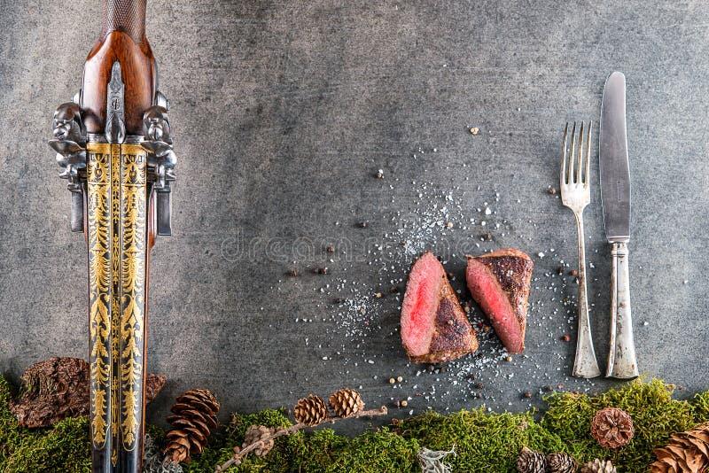 Rotwild- oder Wildbretsteak mit antikem Gewehr, Tischbesteck und Bestandteile mögen Seesalz und -pfeffer, Lebensmittelhintergrund stockbild
