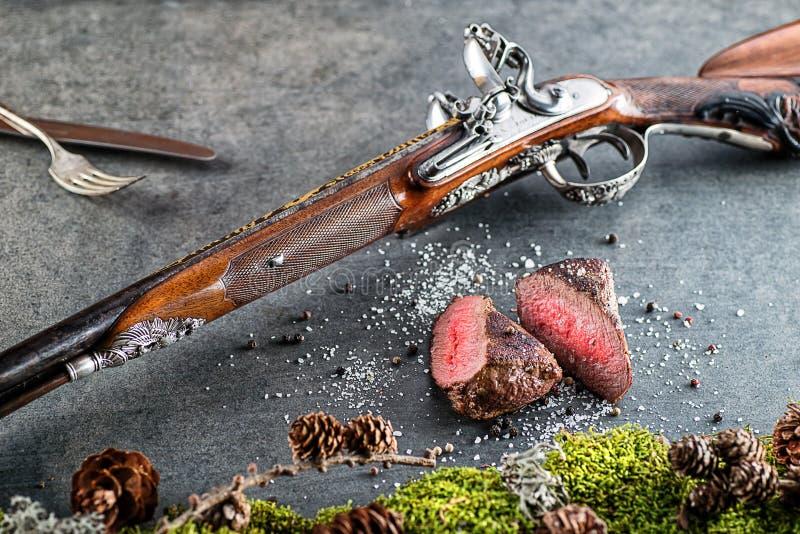 Rotwild- oder Wildbretsteak mit antikem Gewehr und Bestandteile mögen Seesalz und -pfeffer, Lebensmittelhintergrund für Restauran lizenzfreie stockfotos