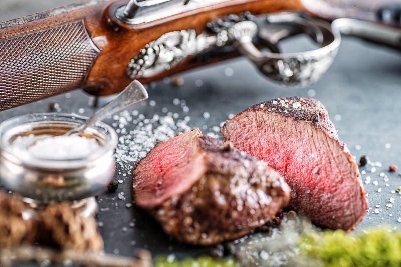Rotwild- oder Wildbretsteak mit antikem Gewehr und Bestandteile mögen Seesalz und -pfeffer, Lebensmittelhintergrund für Restauran stockbilder