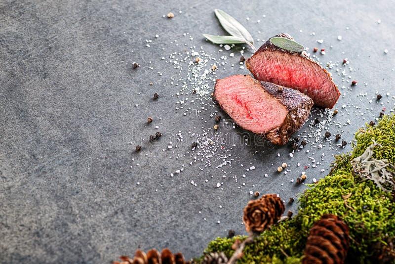 Rotwild- oder Wildbretsteak mit Bestandteilen mögen Seesalz, Kräuter und Pfeffer, Lebensmittelhintergrund für Restaurant oder die stockbilder