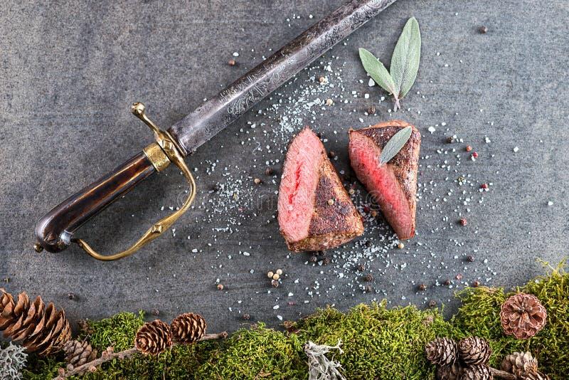 Rotwild- oder Wildbretsteak mit Bestandteilen mögen Seesalz, Kräuter und Pfeffer und Antikensäbel, Lebensmittelhintergrund für Re lizenzfreie stockfotos