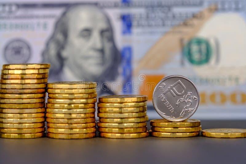 Rouble russe dans la pièce de monnaie roulant vers le bas sur le fond de billet de banque des 100 dollars image libre de droits