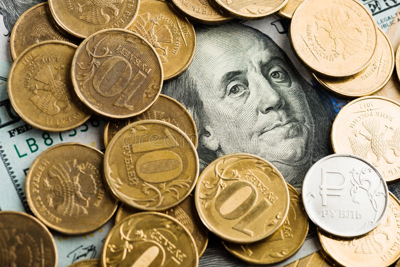 roubles de pièces de monnaie sur des billets de banque des dollars photo stock