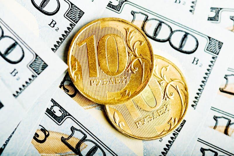 Roubles russes de pièces de monnaie sur des billets de banque des dollars photos stock