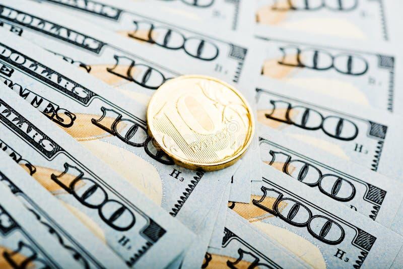 Roubles russes de pièces de monnaie sur des billets de banque des dollars image stock