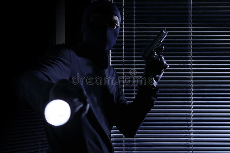 Roubo e extorsão o assaltante mascarado profissional hábil veste um passa-montanhas, guardando uma arma e uma tocha e quebrando n fotografia de stock