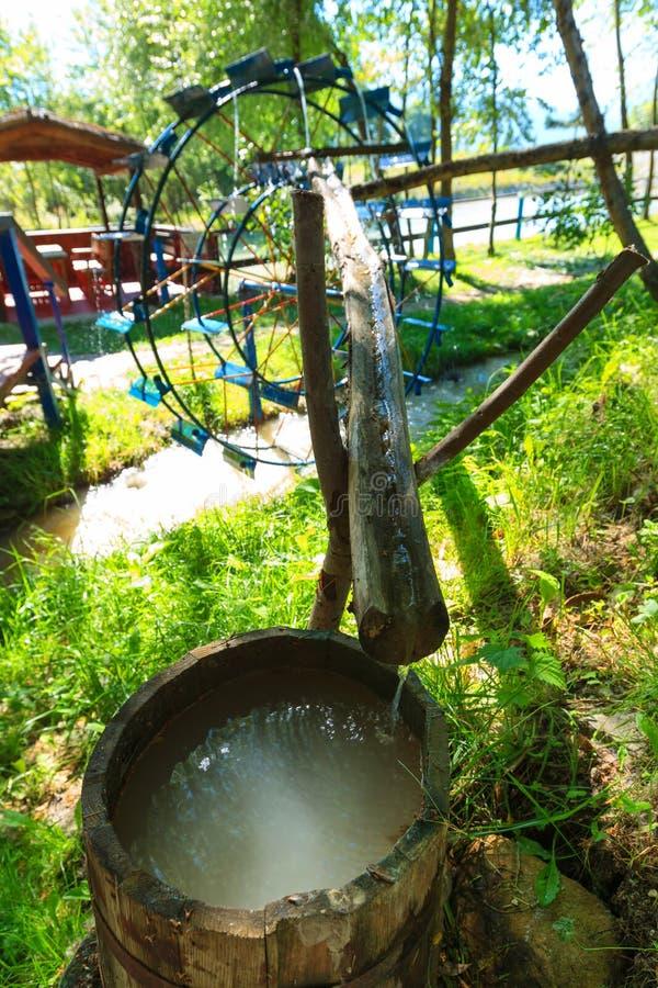Roue d'eau en métal Baril en bois avec de l'eau l'eau propre images libres de droits