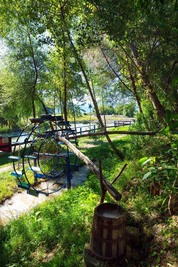 Roue d'eau en métal Baril en bois avec de l'eau l'eau propre photographie stock