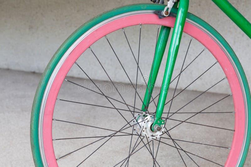 Roue de bicyclette fixe verte de vitesse au bâtiment image stock