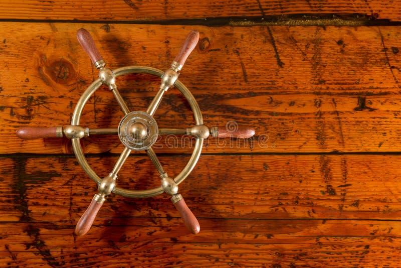 Roue en laiton de bateau sur le bois texturisé image stock