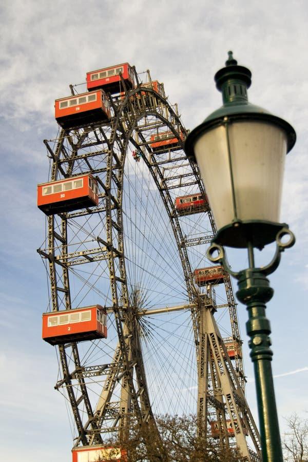 Roue géante d'amusement de parc de prater de Vienne avec les carlingues rouges de la terre avec un réverbère brouillé images libres de droits