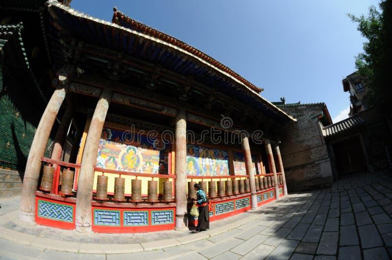 Roues de prière de rotation de femme tibétain image libre de droits