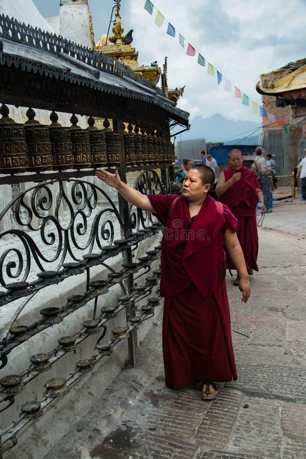 Roues de prière de rotation de moine bouddhiste chez Swayambhunath Stupa à Katmandou Népal photos stock