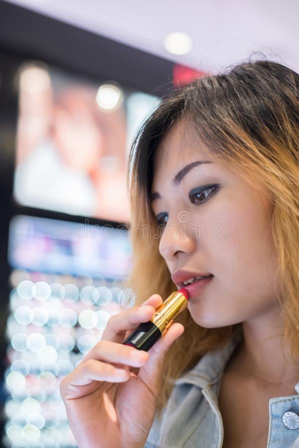 Rouge à lèvres choisi de couleur de belle jeune femme à l'achat aux achats photo libre de droits