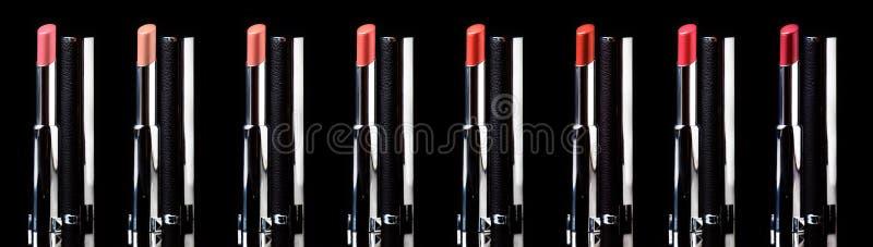 Rouge à lèvres dans l'assortiment, du rouge aux couleurs nues, d'isolement sur le noir, bannière, profondeur de champ photographie stock libre de droits