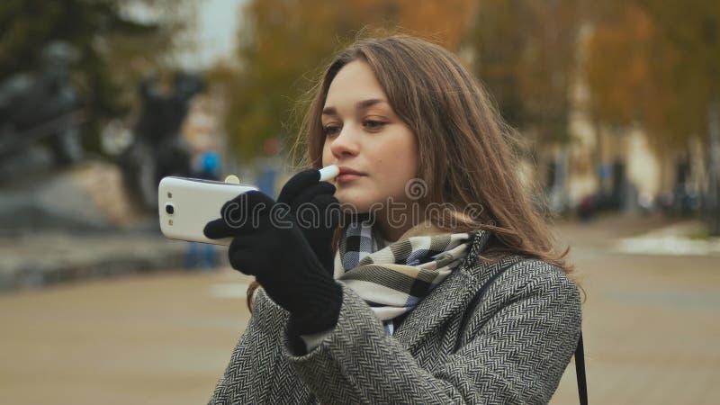 Rouge à lèvres hygiénique de jeune beau rouge à lèvres de fille sur une rue de ville Automne froid photographie stock