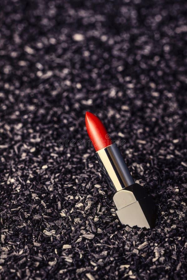 Rouge à lèvres rouge, sur un fond noir de charbon de bois photos libres de droits