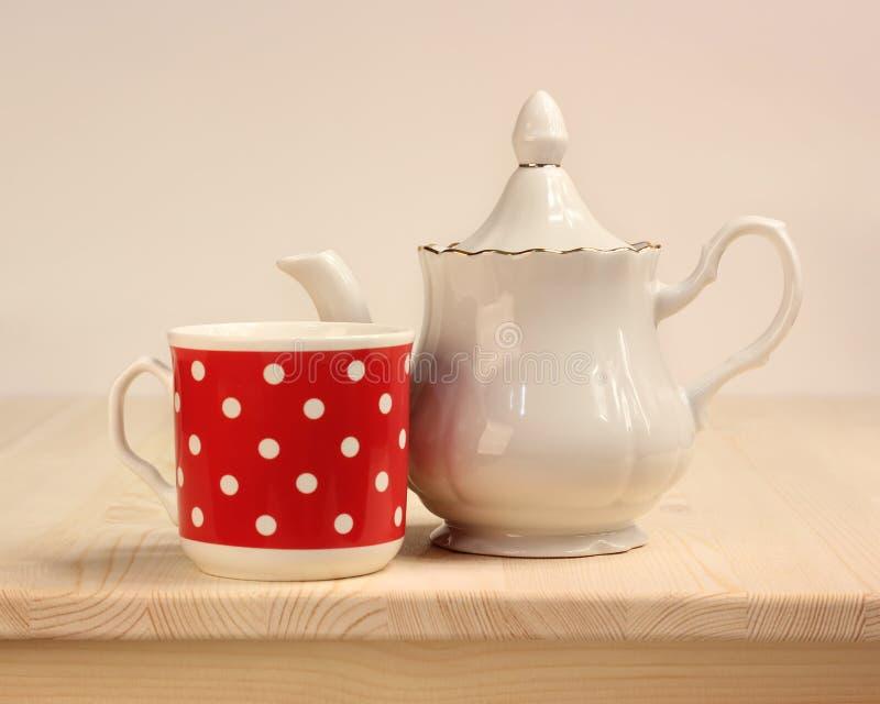 Rouge blanc de théière et de tasse avec des points de polka photos stock