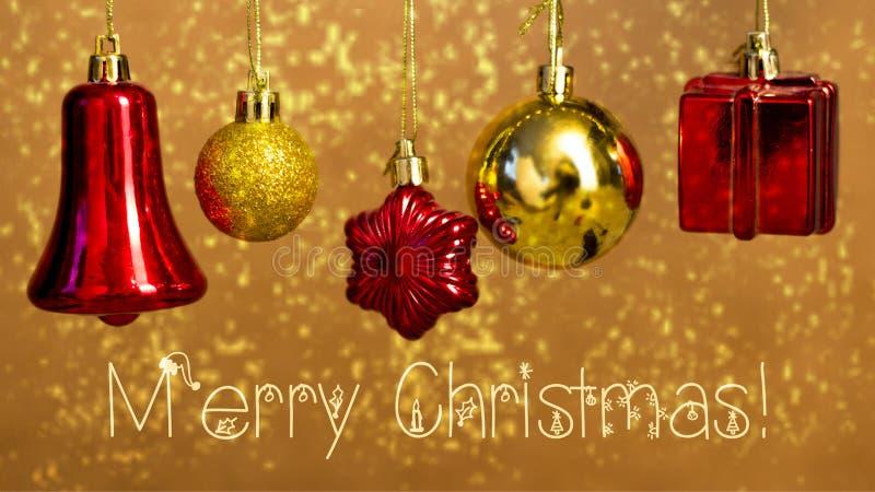 Rouge de carte postale et jouets de Noël d'or accrochant sur un fond en bois images stock