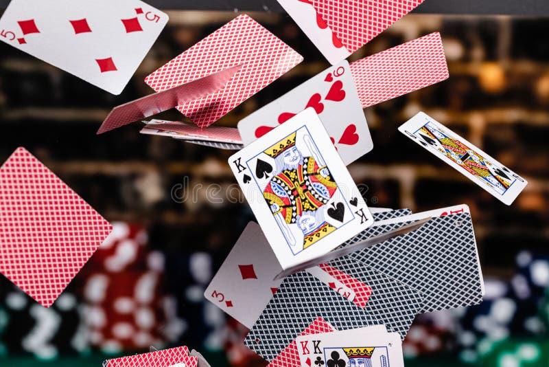 Rouge et bleu a soutenu des cartes de jeu cascadant devant un fond des jetons de poker empilés photos stock