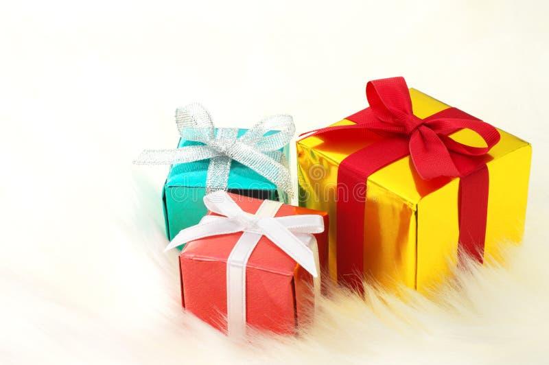 Rouge, or et cadeaux bleus sur la fourrure fausse blanche. photographie stock