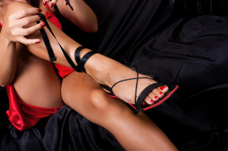 Rouge et noir. Close-up leg girl in a red dress sandals tying on a black background royalty free stock photos