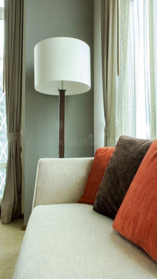 Rouge et oreillers décoratifs de Brown sur un sofa occasionnel de tissu avec la grande lampe blanche dans le salon photos libres de droits