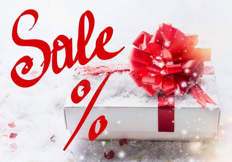 % rouges de lettrage de vente avec le boîte-cadeau blanc, arc rouge sur la neige avec le bokeh et chutes de neige Bon, vente et a photo libre de droits