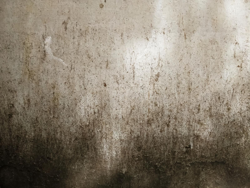 Rough, aged, and decayed concrete surface with dark stains stock image
