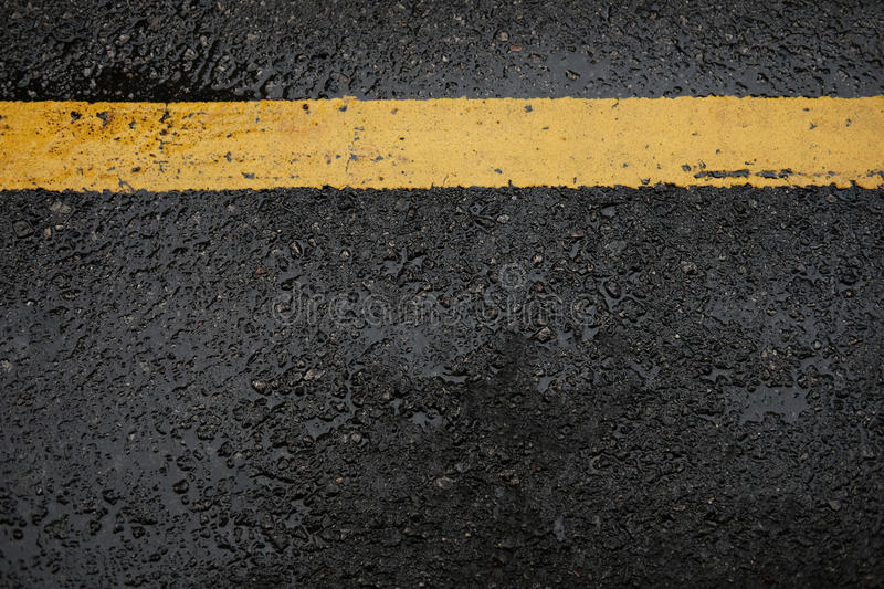 rough black asphalt road and yellow traffic lines ,this image for texture and transport stock photography