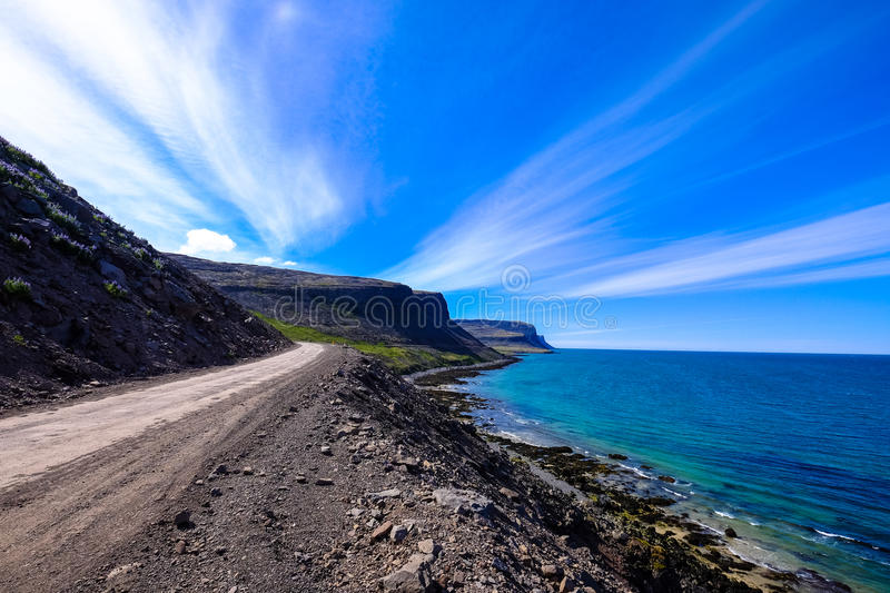 Rough coast road with dramatic sky and cloud stock image