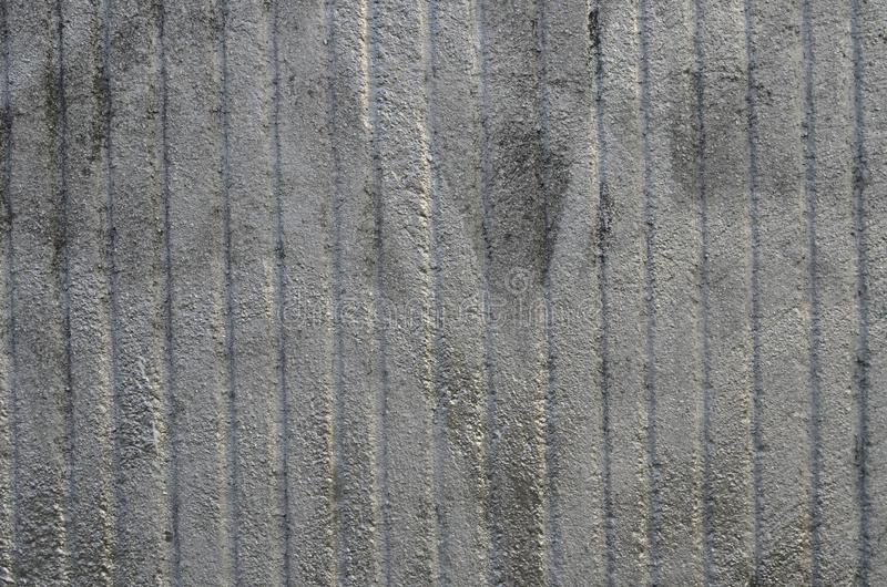 Rough concrete wall airbrushed by silver graffiti paint. Striped concrete wall with rough texture sprayed by graffiti paint of silver color. Background royalty free stock image