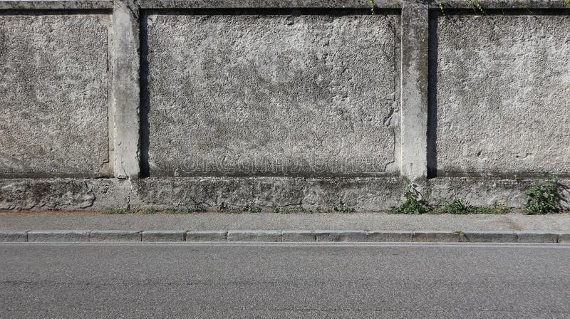 A rough concrete wall with a gray sidewalk and an asphalt road. Urban background for copy space stock images