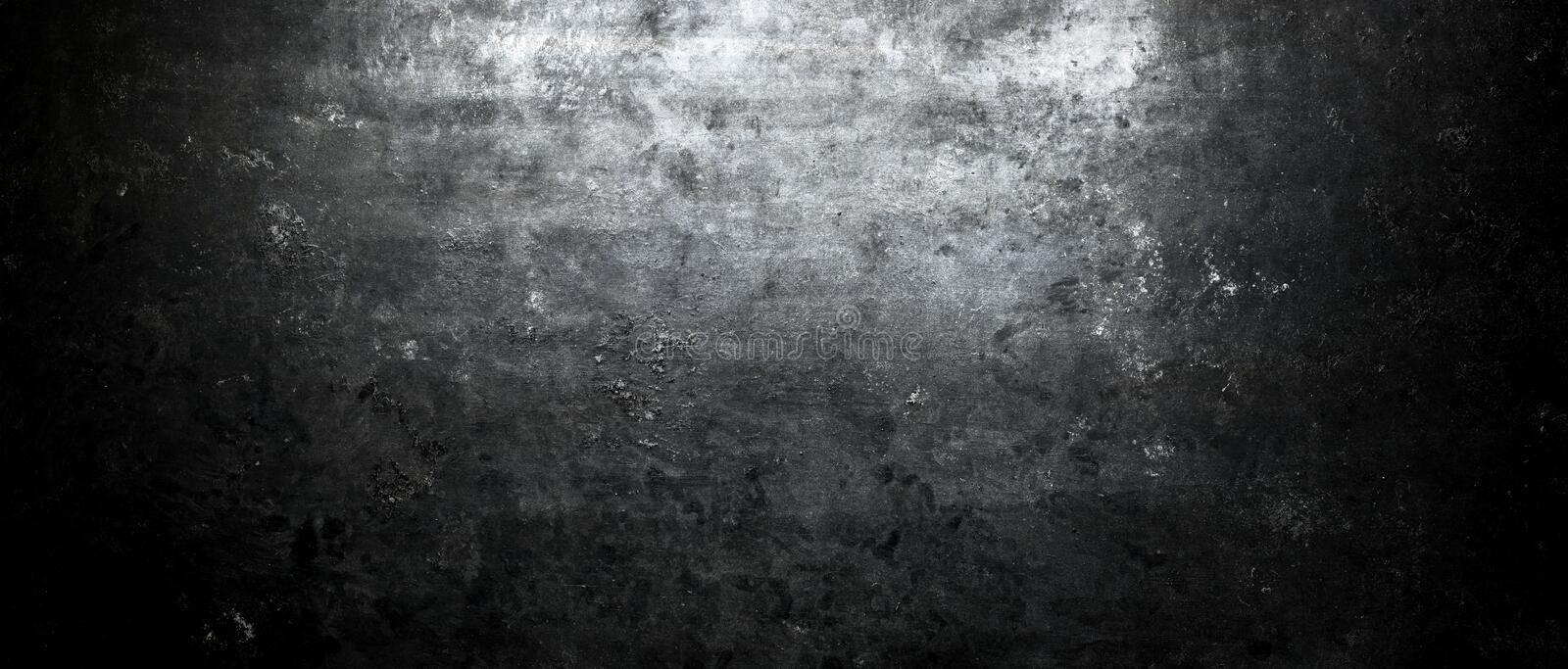 Dark stone wall lit from above by spotlight. Grunge background royalty free stock photo