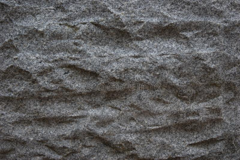 Rough hewn panel of igneous rock with horizontally banded tool marks. Rough hewn panel of grey and white igneous rock with decorative black speckling, and and stock image