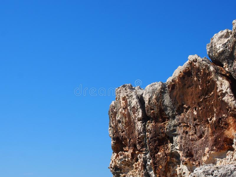 Rough jagged rocky outcrop against a bright blue sunlit sky stock photo