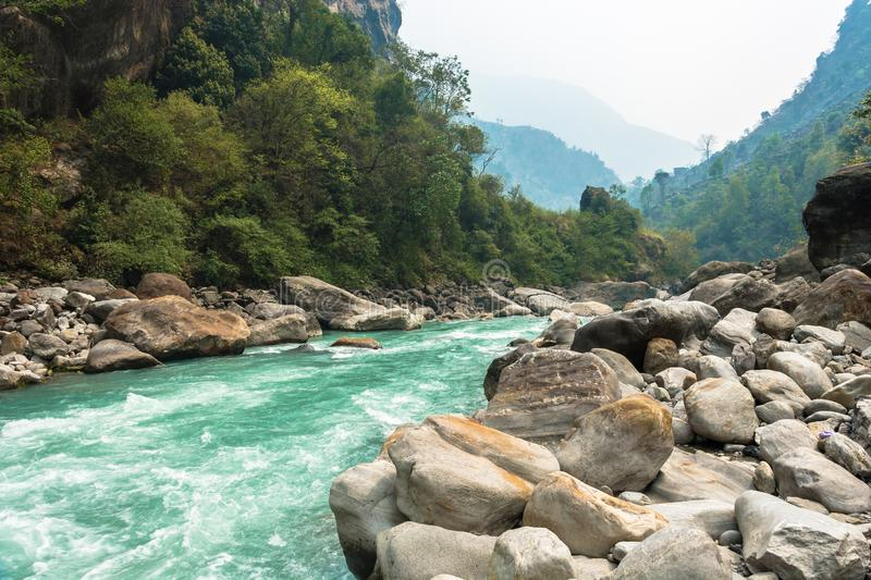 Rough mountain river in the stone banks. Rough mountain river in stone banks on spring day, Himalayas, Nepal royalty free stock image