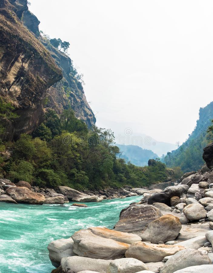 Rough mountain river in the stone banks. Rough mountain river in stone banks on spring day, Himalayas, Nepal royalty free stock photos