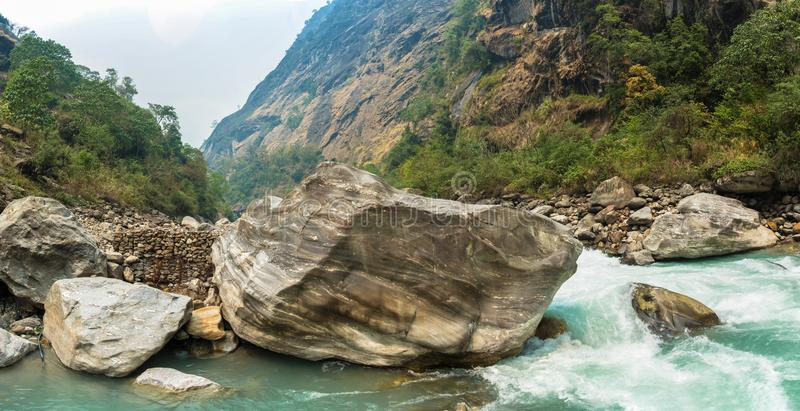 Rough mountain river in the stone banks. Rough mountain river in stone banks on spring day, Himalayas, Nepal stock image