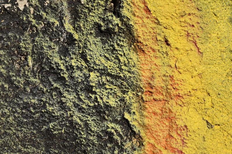Rough painted concrete. Rough concrete wall airbrushed with black and yellow paint royalty free stock photography