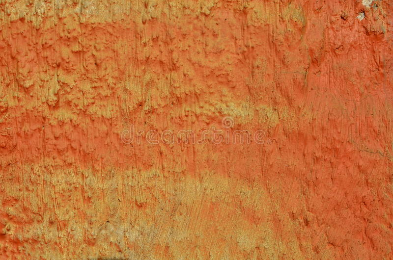 Rough painted plaster. Rough plastered wall airbrushed with orange graffiti paint royalty free stock photo