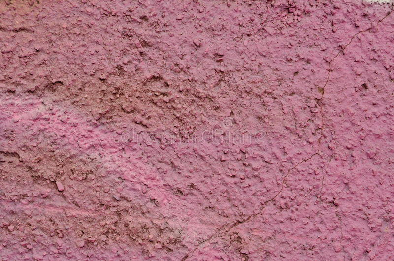 Rough pink wall. Rough plastered wall airbrushed with pink graffiti paint stock images