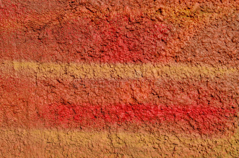 Rough red graffiti paint. Rough bumpy plastered wall airbrushed with red and yellow paint stock photography